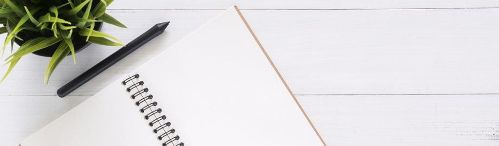 Weißes Notebook mit Pflanze