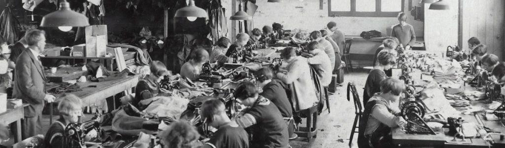 Arbeiter welche in einem Lagerraum an Nähmaschinen sitzen
